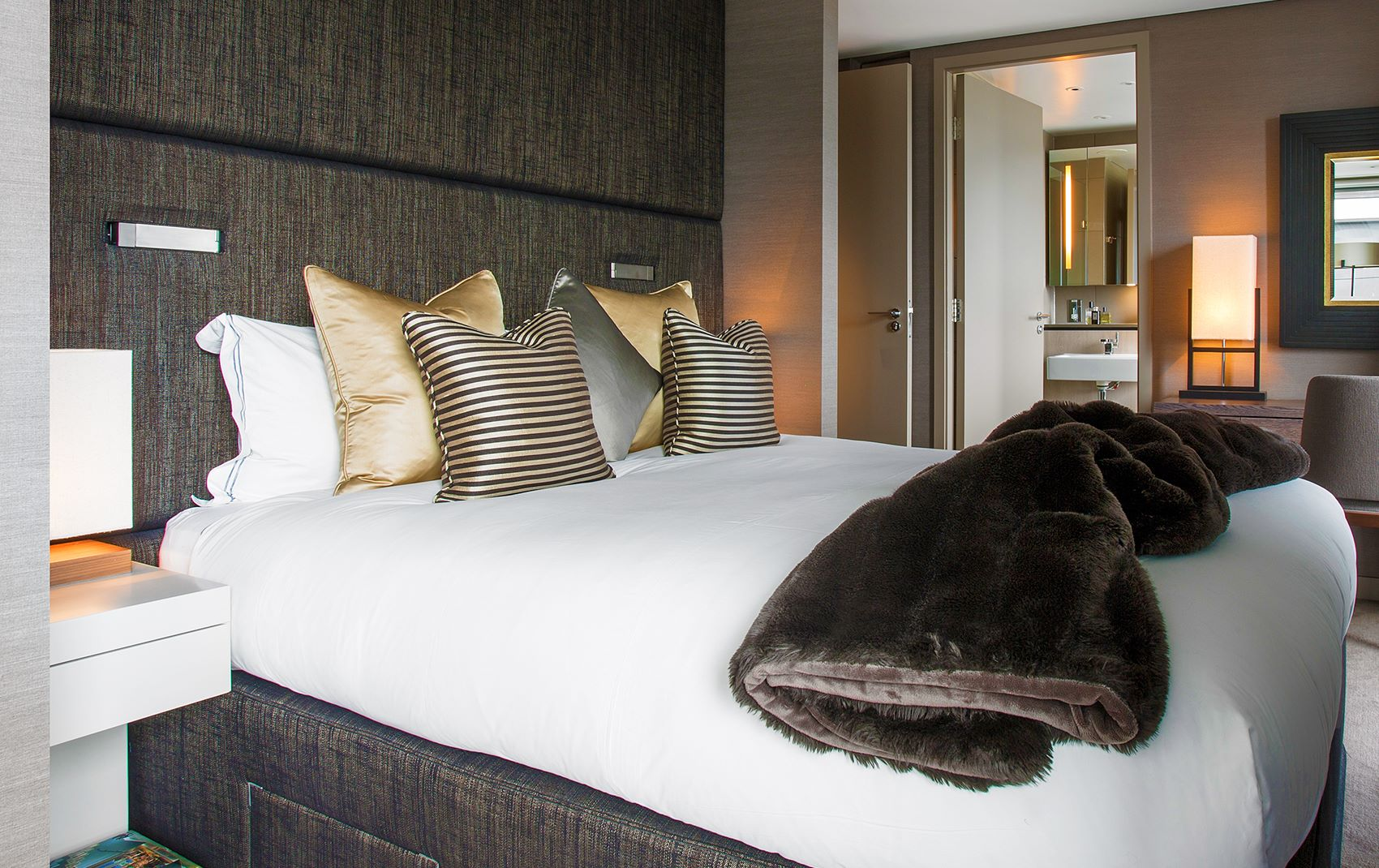 west london penthouse - bed with gold pillows and plush blanket